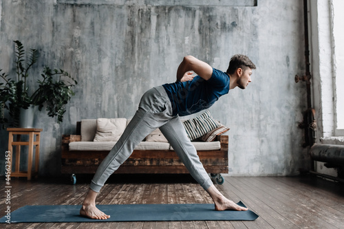 Billede på lærred A young man performing yoga asanas and sports exercises to improve the strength