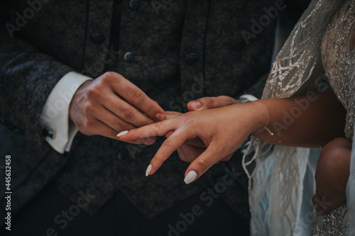 Tela Groom putting the ring on the bride during the wedding ceremony at the church