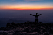 Silhouette Man In The Back With Arms Open Standing On Viewpoint At Nodular Stones Mountain Peak Or Lan Hin Poom During Sunset, Phu Hin Rong Kla National Park In Phitsanulok, Thailand, Freedom  Concept