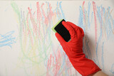 Woman erasing child's drawing from white wall, closeup