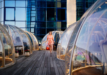At Sunset. Woman In A Pink Dress Strolls Along The Roof Between The Igloo Tables