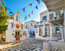 Beautiful Morning View Of Small Square Decorated For Some Celebrations With Flags In Typical Greek Town. Greek Orthodox Church, Whitewashed Houses.