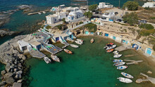 Aerial Drone Photo Of Picturesque Small Fishing Harbour Of Mandrakia With Traditional Boat Houses Called Syrmata And Anchored Fishing Boats, Milos Island, Cyclades, Greece