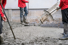 Four Worker Team Working Wet Cement  On Floor By Use Trowel With Long Tools Spreading Poured Concrete For Strong Street After Dry.