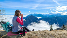 A Woman In Hiking Outfit Sipping A Tea From Thermos With The Panoramic View From The Top Of Alpine Peak In Austria. The Area Is Shrouded In Thick Clouds. A Few Peaks Popping Out From The Clouds. Happy