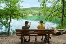 The Boys Rest After A Long Walk At Plitvice Lakes Near The Lake And Looking In To The Distance While One Shows The Other Something