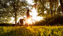 Adventurous White Cacasusian Woman With A Bicycle In A Park. Sunny Summer Sunset. Barnston Island, Vancouver, British Columbia, Canada. Adventure Journey Concept