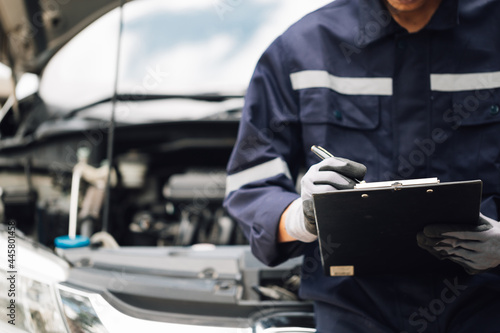 Fotografia Car service, repair, maintenance concept,auto mechanic man or Smith writing to the clipboard at workshop, technician doing the checklist for repair machine a car in the garage,banner