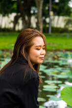 Portrait Of A South Asian Young Female Posing Beside A Pond With Water Lilies In The Park