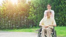 車椅子を押す介護ヘルパー