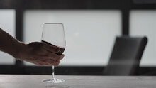 Man Take Red Wine In Wineglass From White Oak Table With Copy Space