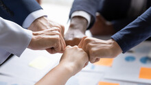 Diverse Business Team Making Group Fist Bump. Employees Engaged In Teamwork, Keeping Community Spirit, Expressing Solidarity, Trust, Unity, Friendship. Close Up Of Multiethnic Hands