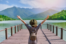 Traveler Girl Backpacker With Open Raised Arms Standing Alone On Pier And Staring At Lake And Mountains. Enjoying Free Moment Life And Serene Quiet Peaceful Atmosphere In Nature. Back View