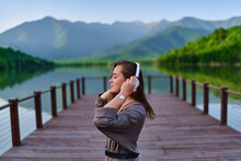 Girl Traveler Listening To Calm Music On Wireless Headphones Standing Alone On Pier With Lake And Mountains View And Enjoying Serene Quiet Peaceful Atmosphere