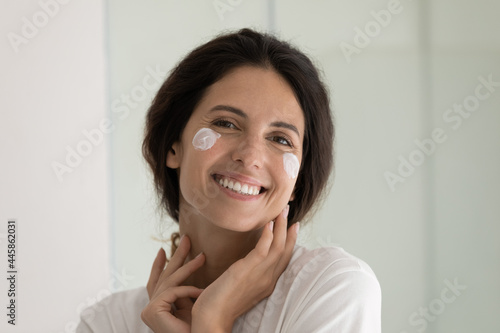 Obraz na plátně Headshot portrait of happy hispanic woman pampering face skin with natural cosmetic daily care product creme serum mask