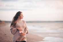 Smiling Pregnant Woman Wear Knit Cardigan Hold Baby Shoes Posing Over Sea Background Close Up. Looking Away Forward. Motherhood. Maternity. Healthy Lifestyle. Happiness.