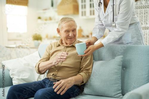Obraz na plátně Elderly man going to drink a hot drink at home