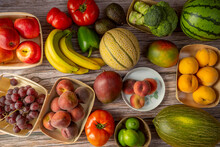 Seasonal Fruits And Vegetables In Bowls, Fruits And Plates Or Directly On The Wooden Board. Bananas, Melons, Red Grapes, Nectarines, Broccoli And Tomatoes, Avocados And Peppers