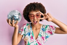 Young Hispanic Girl Wearing Summer Style Holding Disco Ball Winking Looking At The Camera With Sexy Expression, Cheerful And Happy Face.