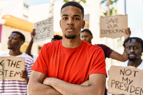 Foto Young activist man with arms crossed gesture standing with a group of protesters holding banner protesting at the city