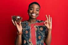 Young African American Woman Holding Bowl Of Star Anise Doing Ok Sign With Fingers, Smiling Friendly Gesturing Excellent Symbol