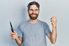 Caucasian Man With Beard Holding Pocket Knife Screaming Proud, Celebrating Victory And Success Very Excited With Raised Arms