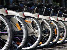 Closeup Shot Of A Row Of Bicycle Wheels At A Parking Area