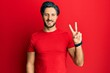 Leinwandbild Motiv Young hispanic man wearing casual red t shirt showing and pointing up with fingers number two while smiling confident and happy.