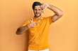 Leinwandbild Motiv Young hispanic man wearing casual yellow t shirt smiling making frame with hands and fingers with happy face. creativity and photography concept.