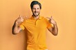 Leinwandbild Motiv Young hispanic man wearing casual yellow t shirt smiling cheerful showing and pointing with fingers teeth and mouth. dental health concept.