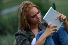 Concerned Confused Young Woman Staring At Her Tablet
