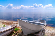 White Fishing Boat Rest On Shore. Old Rusty Winch And Boat On Beach. Beautiful Summer Landscape On The River Or Lake Or Sea. Boat On The River Bank.