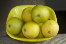 Closeup Shot Of Yellow And Greenish Sweet Lemons In A Yellow Plastic Tray
