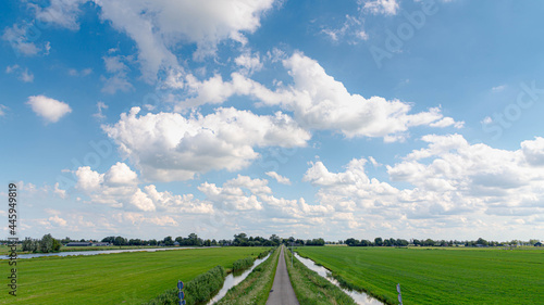 Fotografie, Obraz Summer countryside landscape with flat and low land under blue sky, Typical Dutch polder and water land with green meadow, Small canal or ditch on the field along the road, Noord Holland, Netherlands