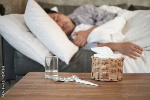 Photo Asian man is absent from work and sick leave because of illness, takes temperature by thermometer, takes medicine, and sleeps in blankets on sofa at home, tissues, and capsule pills on the table