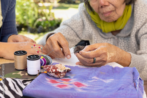 Fototapeta Elderly woman and daughter in the needle crafts occupational therapy for Alzheim