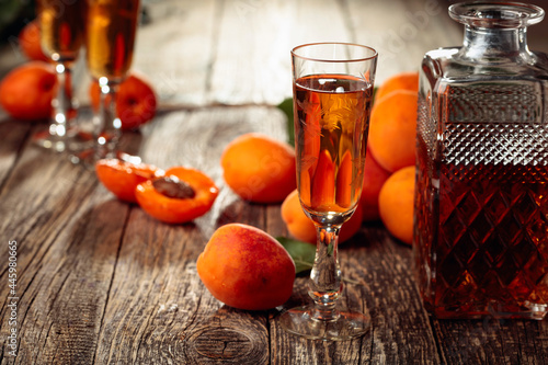 Apricot liquor and fresh apricots on a old wooden table. Fotobehang