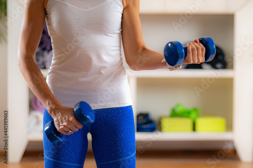 Woman Exercising with Dumbbells. Exercise for Biceps. Fototapet