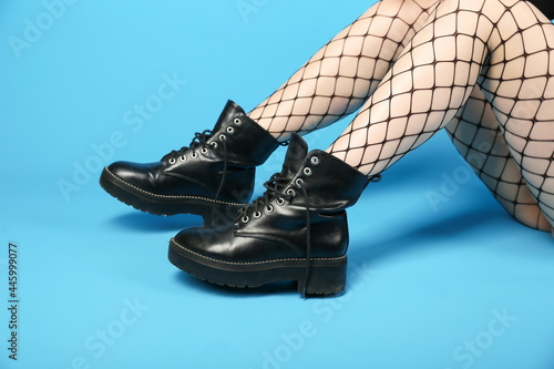 Fotografia woman legs wearing fishnet pantyhose and combat boots on blue background