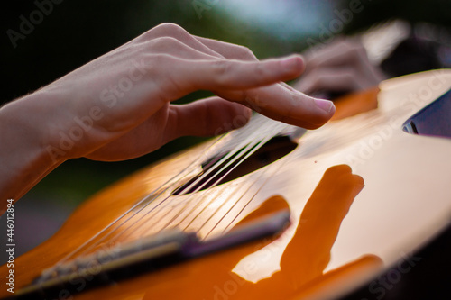 Young man playing a guitar hands close up