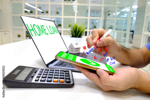 Fotografiet A man holding a smartphone in his left hand, a pen in right hand and pays off a home loan online