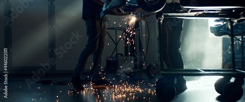 Fotografia CU Sparks falling on the ground as mechanic welding a go kart car inside garage