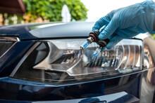 Mechanic Hold Car Halogen Light Bulb For Repair Against Headlight Auto In Background