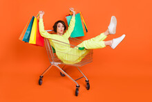 Portrait Of Attractive Amazed Cheery Girl Sitting In Cart Holding Bags Pout Lips Isolated Over Bright Orange Color Background