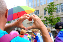 Members Of LGBTq Movement, Gay Pride Parade In City With Rainbow Flags, Demonstration Of People, Mass March Of Lesbian, Gay, Bisexual, Minority Festival, Male Hands Close Up Gesture Heart