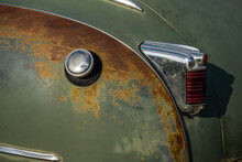 Chromium Plated Rear Lamp Of A Green Classic Car Before Restoration. Photo Taken In Natural Light.