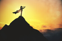 Businesswoman With Telescope Standing On Creative Backlit Mountain And Sunset Background With Mock Up Place For Your Advertisement. Leadership And Tomorrow Concept.