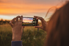 Person Taking Pictures Of A Field At Sunset Golden Hour