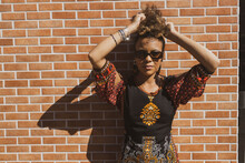 Beautiful African American Woman Wearing Sunglasses Leaning Against  Orange Bricks Wall Tiding Up Her Curly Hair. Copy Space For Text.