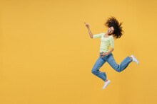 Full Size Body Length Happy African American Young Woman 20s Wears Green Shirt Jump Do Guitar Gesture Keep Eyes Closed Isolated On Yellow Background Studio Portrait. People Emotions Lifestyle Concept